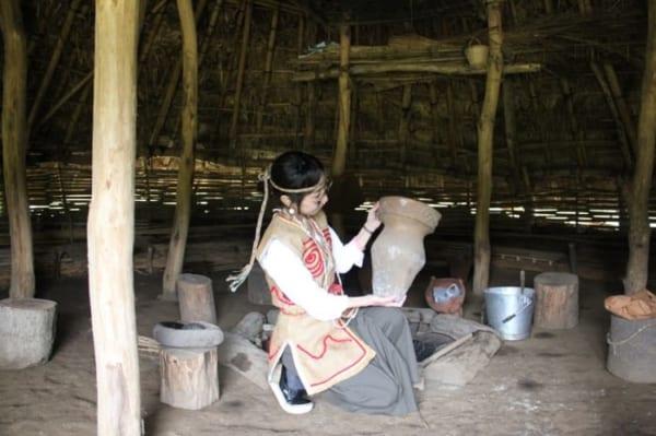 加曽利貝塚の復原住居で縄文土器のレプリカを持ち、縄文服を着ました
