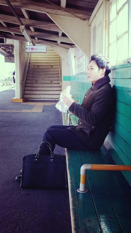 コッペパンを駅のホームで食べる男性。