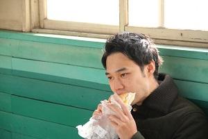 日本列島パン食い協奏のコッペパンをほおばる男性。