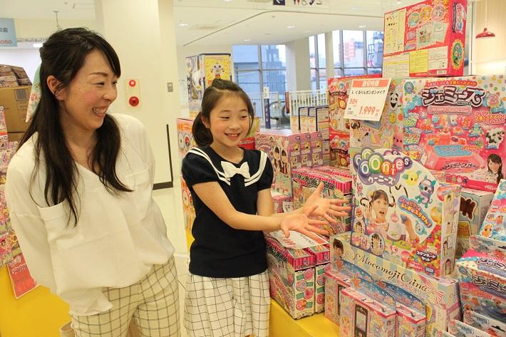 安いアウトレットのおもちゃ屋さんで買い物をするママと子ども
