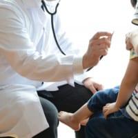 小児科で先生の診察を受ける親子