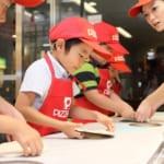 キッザニア東京のピザショップパビリオンでピザ作り体験をする男の子