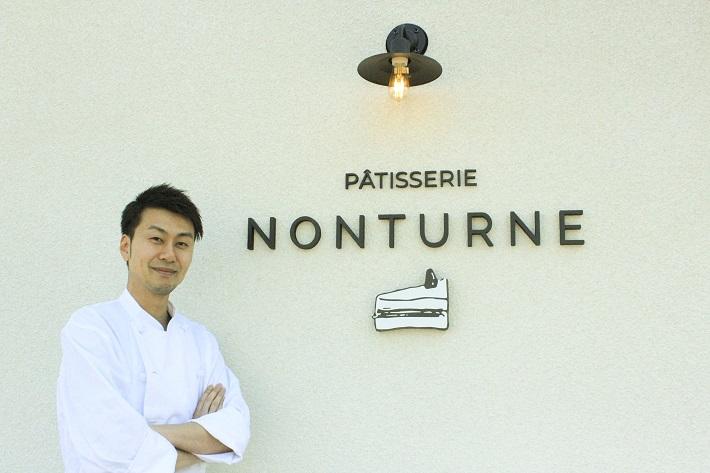 千葉県柏市手賀の杜にオープンしたケーキ屋さんパティスリーノンターンの看板前に立つオーナーシェフの丹野さん
