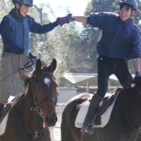 アニベジの騎手課程で手を繋いで騎乗練習を行う男性二人