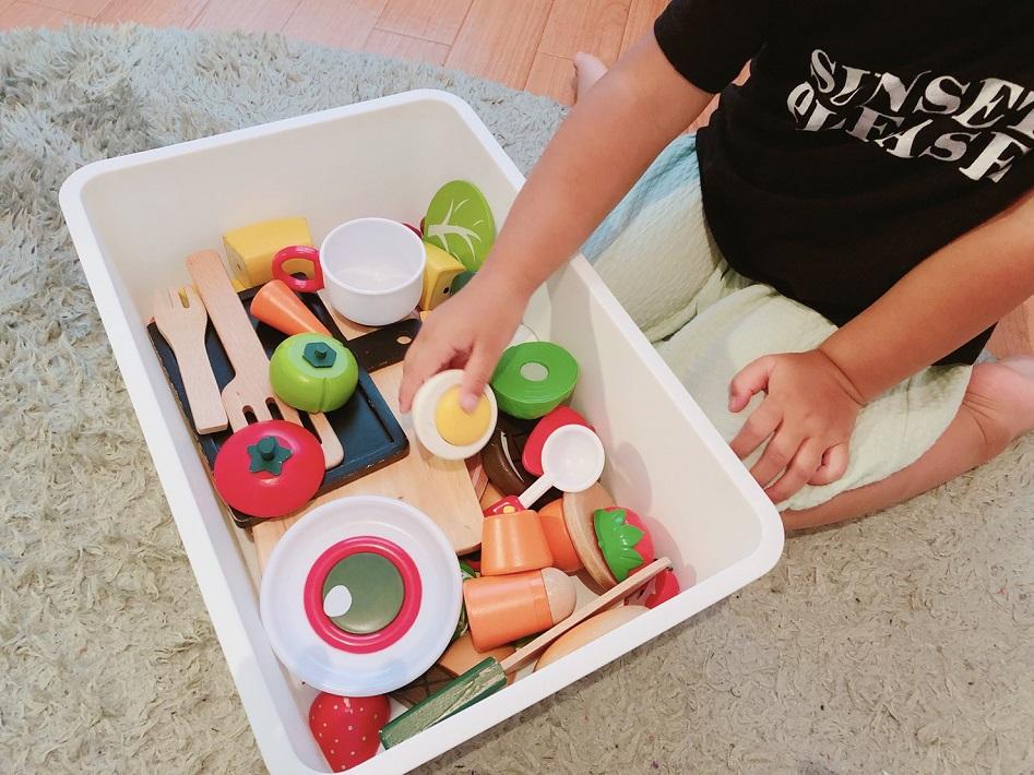 おままごとのおもちゃを手に取る女の子