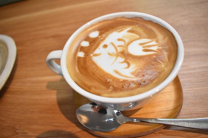 かわいい魚のラテアートがあしらわれたちいさな箱カフェのカフェラテ