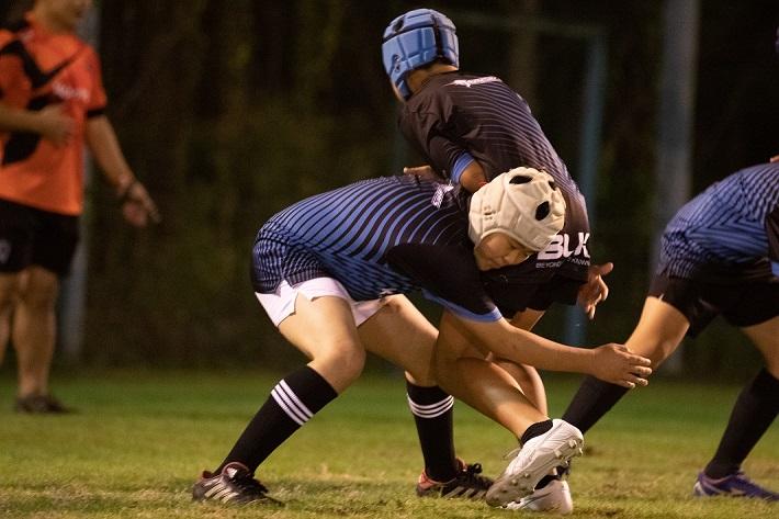 ラグビーをする少年タックル