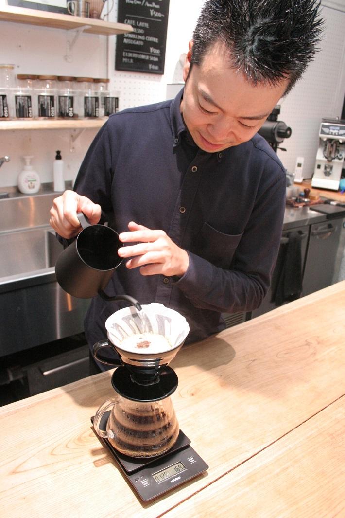 コーヒーにお湯を注ぐバリスタ