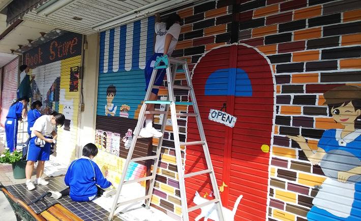 商店街のシャッターに絵を書く子ども