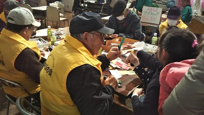 おじいちゃんと折り紙で遊ぶ子ども