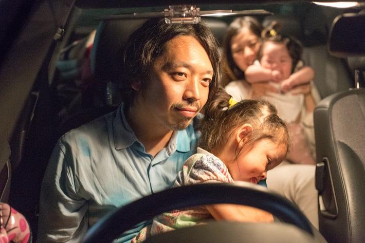 ドライブインシアターで映画を観る車中のファミリー
