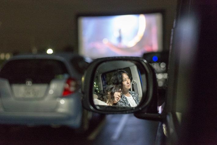 ドライブインシアターでサイドミラーに写る映画鑑賞中のカップル